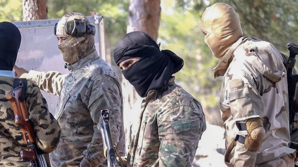 Abu Salman Belarus, the head of Malhama Tactical, with members of Tahrir al-Sham, an al-Qaeda affiliate, during a weapons training near Idlib, Syria on November 14. [File]