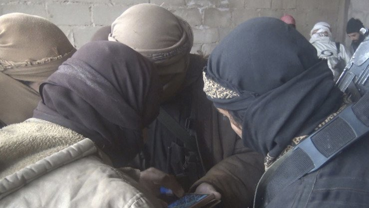 A photo published by IS on Telegram on December 13 shows a group of its fighters huddling around a smartphone in Syria. [File]