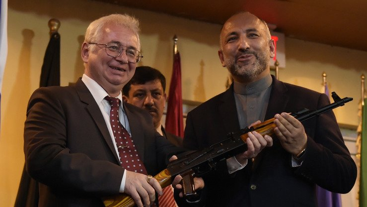 Former Russian Ambassador to Afghanistan Alexander Mantytskiy hands over a AK-47 rifle to Muhammad Hanif Atmar during a ceremony at a military airfield in Kabul on February 24, 2016. Atmar is attending this week's conference in Moscow and is running against Afghan President Ghani in the upcoming presidential elections. [Shah Marai/AFP]