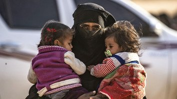 "A fully veiled woman holds two little girls against her chest as hundreds of civilians, who streamed out of ""Islamic State"" (IS)'s last Syrian stronghold, walk towards a screening point for new arrivals run by US-backed Syrian Democratic Forces (SDF) outside Baghouz, Syria, March 5. [Delil Souleiman/AFP]"