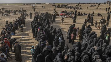 "Civilians evacuated from ""Islamic State"" (IS)'s embattled holdout of Baghouz, Syria, wait at a screening area held by the US-backed Kurdish-led Syrian Democratic Forces (SDF) March 5. [Bulent Kilic/AFP]"