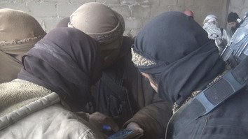 "A photo published by ""Islamic State"" (IS) on Telegram December 13 shows a group of its fighters huddling around a smartphone in Syria. [File]"