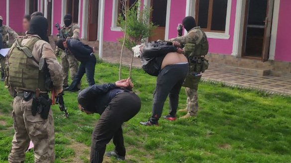 KNB forces lead out suspected extremists whom they arrested in a raid in Shymkent in April. [KNB]