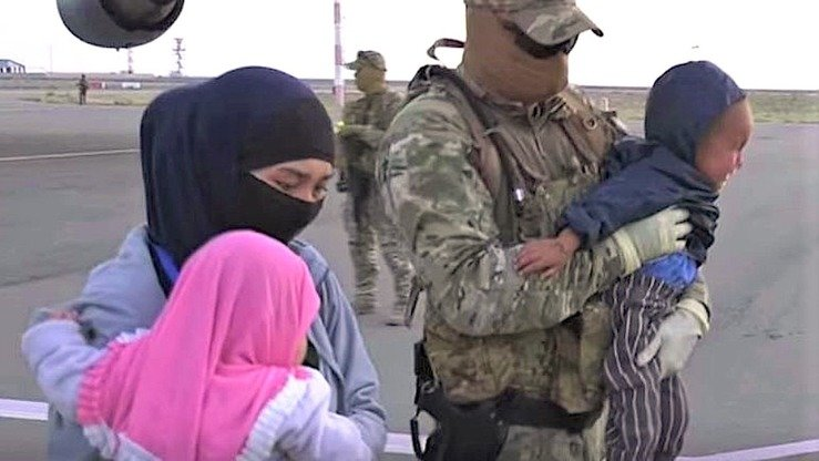 A woman with children, accompanied by Kazakh special forces, walks to a plane in Syria during Operation Jusan-2 (Bitter Wormwood 2), which occurred May 7 and 9. The screenshot is from a KNB video.