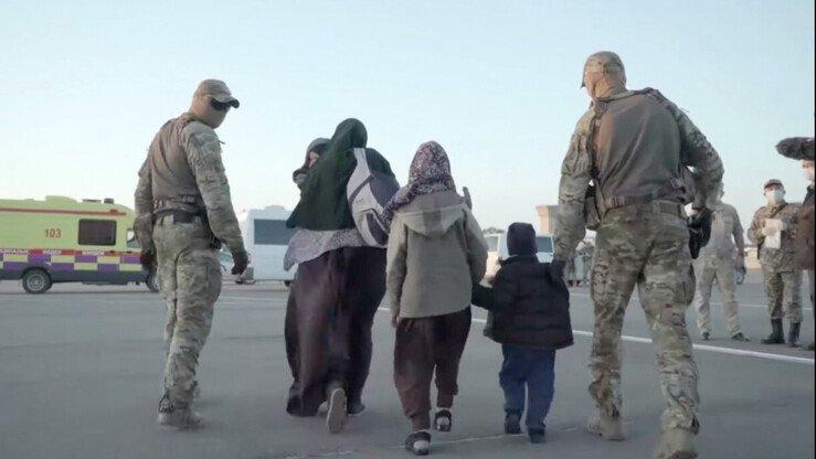 Представители казахстанских сил безопасности сопровождают семью после одной из операций по репатриации своих граждан в начале этого года. [Архив]