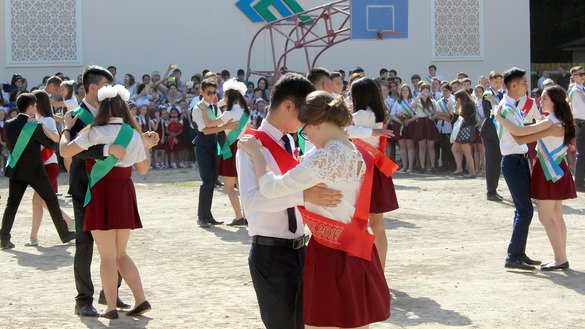 "Tashkent schoolchildren May 25 dance to the ""Last Bell' on their completion of 9th grade. Starting with the next school year, 9th-graders will have a choice -- either remain in high school for two more years or enter a vocational college or academic lycée. [Maksim Yeniseyev]"