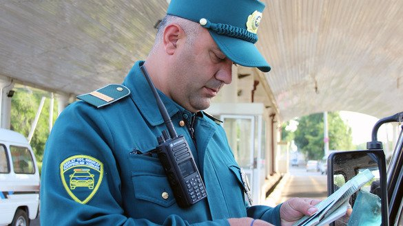 A traffic policeman checks a motorist's documents in Tashkent in August 2014. [Maksim Yeniseyev]